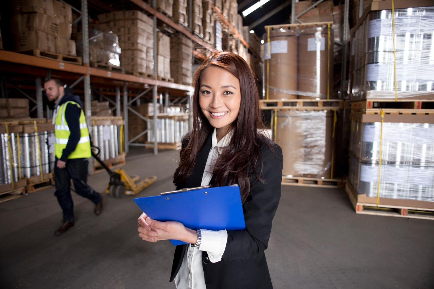 A manager takes stock of the warehouse with a blue clipboard.