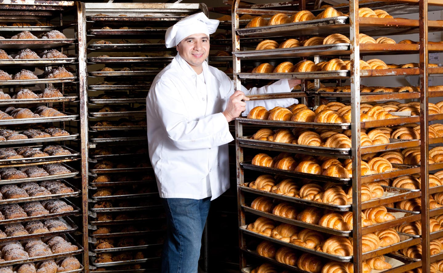 A baker stands next to one of many racks filled with baked goods.
